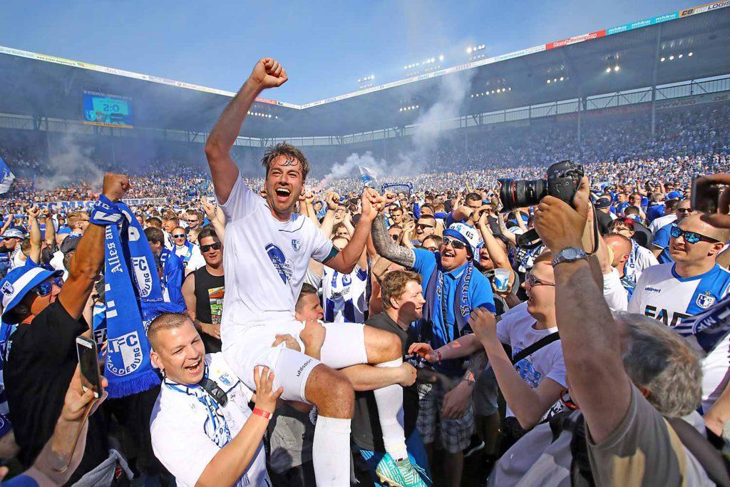 Fans und Fußballer feiern den Aufstieg des 1. FC Magdeburg in die 2. Bundesliga