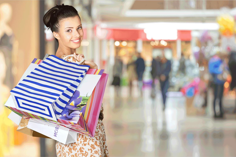 Lächelnde Frau beim Einkaufsbummel mit Einkaufstüten