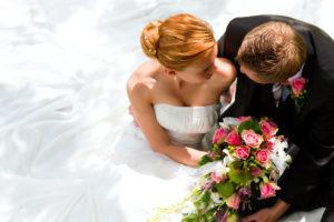 Ein Hochzeitspaar hält sich in den Armen. Die Braut im weißen Hochzeitskleid, der Bräutigam im Anzug. In ihren Händen halten sie einen Blumenstrauß mit pastellfarbenen, rosaroten Blumen.