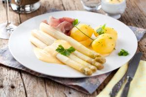 Ein Klassiker der deutschen Küche: weißer Spargel mit Kartoffeln und Schinken auf Sauce Hollondaise.