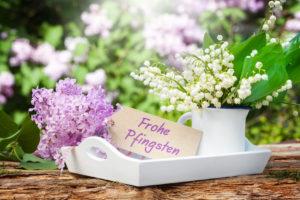 Ein Tablet, darauf frische Blumen und ein Schild mit der Aufschrift Frohe Pfingsten.