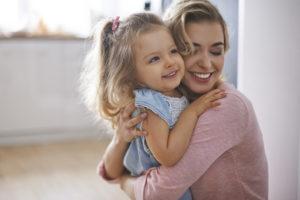 Tochter und Mutter umarmen sich lächelnd.
