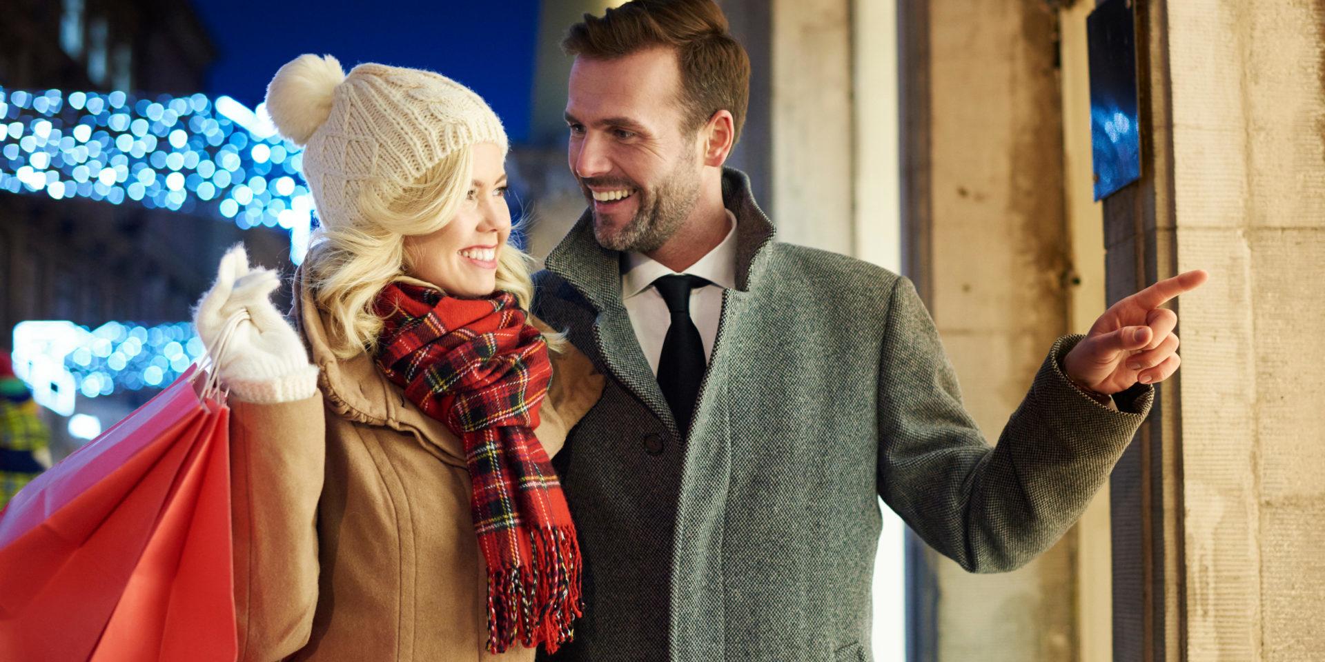 Paar geht zu Weihnachten einkaufen und steht vor einem Geschäft.
